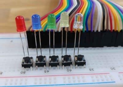 Jumper wires verbonden op breadboard met LED's en pushbuttons